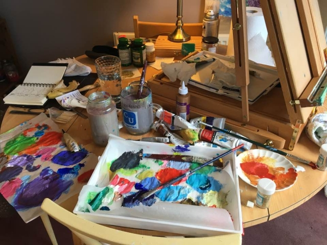 Wendy Dashwood's kitchen table with paints and easel, water and brushes.